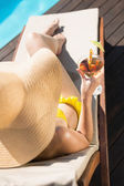 Beautiful woman holding drink by swimming pool — Foto de Stock