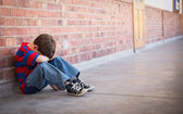 Sad pupil sitting alone in corridor — Foto Stock