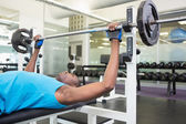 Young man lifting barbell in gym — ストック写真