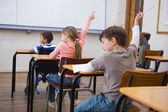 Levantando las manos durante la clase de los alumnos — Foto de Stock