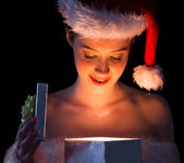 Woman in santa outfit opening a gift — Stock Photo