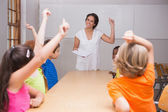 Pupils raising their hands in class — Stock Photo