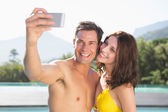 Couple taking picture of themselves by pool — Stock Photo