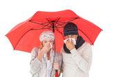Couple in winter fashion sneezing under umbrella — Stock Photo