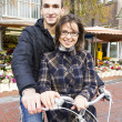 Happy young couple with bicycle near the flower market — Stock Photo