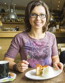 Smiling woman at cafe eating apple cake dessert with cream — Stock Photo