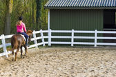 Young girl riding a running horse — Stock Photo