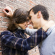 Portrait of love couple outdoor looking happy against wall backg — Stockfoto #17783049