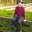 Cute teenage  boy in helmet and boots for horse riding sitting n - 图库照片