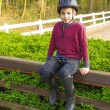Cute teenage  boy in helmet and boots for horse riding sitting n - Zdjęcie stockowe