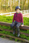 Cute teenage boy in helmet and boots for horse riding sitting n — Stock Photo