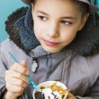 Royalty-Free Stock Photo: Cute teenage boy eating ice cream with chocolate topping