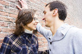 Portrait of love couple outdoor looking happy against wall backg — Photo