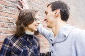 Porträtt av love par utomhus ser glad mot väggen backg — Stockfoto