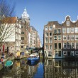 Stock Photo: Blue boat on channel in Amsterdam. Typical Amsterdam architectur