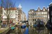 Blue boat on channel in Amsterdam. Typical Amsterdam architectur — Stock Photo