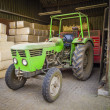 Foto Stock: Green tractor sheltered against background of packages with