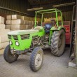 Green tractor sheltered against the background of packages with — Zdjęcie stockowe