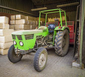 Green tractor sheltered against the background of packages with — Stok fotoğraf
