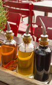 Balsamic vinegar bottles and condiments on the table in an open — Stock Photo