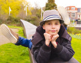 Cute teenage boy lying on the parapet at the park — Stock Photo