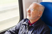 Relaxed old man sitting near the window in the carriage — Stock Photo