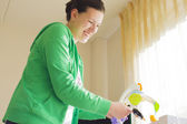 Mother runs a music windup toy over the baby's crib — Stock Photo