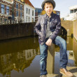 Cute teenage boy in hat (full-length portrait) against canal bac — Stock Photo #24019235