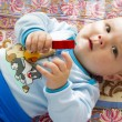 Royalty-Free Stock Photo: Adorable baby with a toy in the hand on a colored blanket