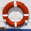 Orange ring buoy hanging on white painted boat — Stock Photo