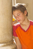 Tired of the heat boy leaned against pillar — Stock Photo