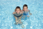 Two happy friends swimming in the pool — Stock Photo