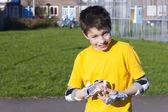 De jongen zet op aandachtig wieltjes bescherming voor kit — Stockfoto
