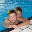 Stock Photo: Activities on the pool. Cute boys swimming and playing in water