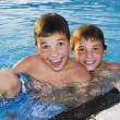 Activities on the pool. Cute boys swimming and playing in water — Stock Photo #25371265