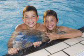 Activities on the pool. Cute boys swimming and playing in water — Stock Photo