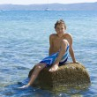 Cute eleven years old boy sitting on a rock in the sea — Foto de Stock