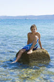 Cute eleven years old boy sitting on a rock in the sea — Stock Photo