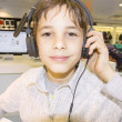 Stock Photo: Portrait of sweet young boy listening to music on headphones