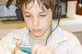 Porträtt av en söt ung pojke lyssna på musik i hörlurar — Stockfoto