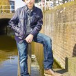 Cute teenage boy in hat (full-length portrait) against canal bac — Stock Photo #30352451