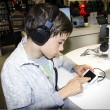 Portrait of a sweet young boy listening to music on headphones — Stock Photo