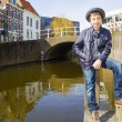 Cute teenage boy in hat (full-length portrait) against canal background — Stock Photo #30831051