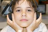 一个甜美的小男孩,听音乐头戴式耳机的肖像 — 图库照片