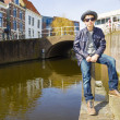 Cute teenage boy in hat (full-length portrait) against canal background — Stock Photo #31691597