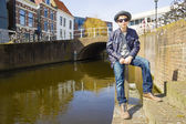 Cute teenage boy in hat (full-length portrait) against canal background — Stock Photo