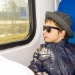 Handsome boy in sunglasses rides on a train — Stockfoto