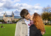 Outdoor happy couple kissing in Museumplein, Amsterdam — Stock Photo