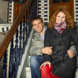 Young couple sitting on a Dutch porch outdoors in autumn. — Foto de Stock