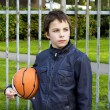 Young basketball player holding ball against iron fence at p — Foto de stock #36374487